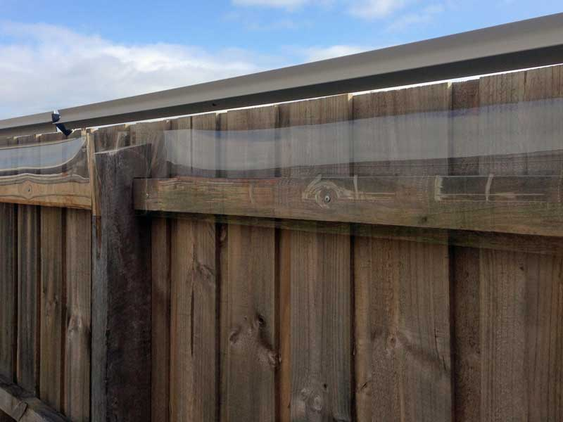 oscillot on timber fence plus acrylic shield to enclose the exposed rail near top of fence 2 existing fence cat