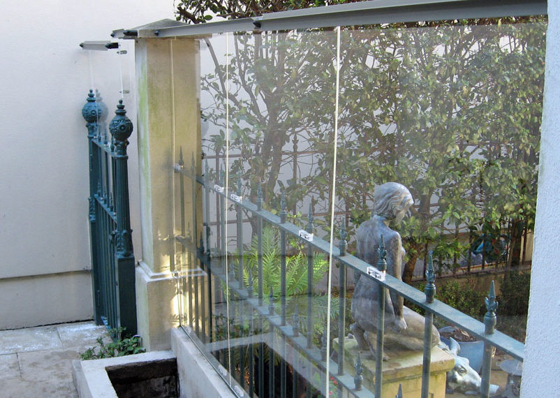 Clear acrylic was used to raise the height of this fence while still allowing natural light into the courtyard.
